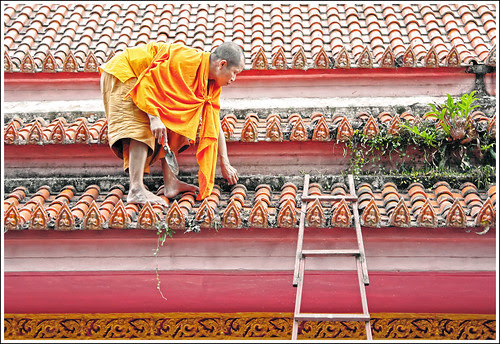 Monk cleaning temple roof at Wat Bang Riang