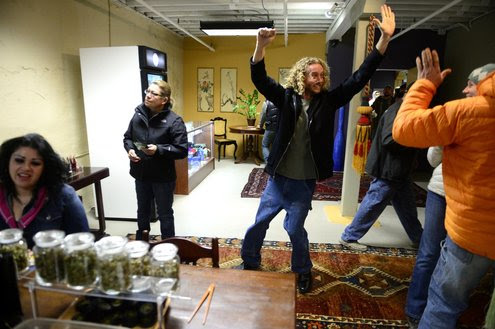 Justin Auchenbach of Casper, Wyo., gives a high-five inside LoDo Wellness in Denver in anticipation of making a marijuana purchase during Colorado's first day of recreational pot sales on Wednesday.