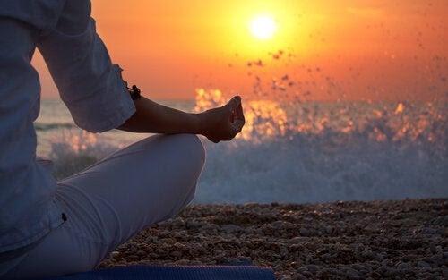mujer-haciendo-meditacion-en-la-arena-de-la-playa