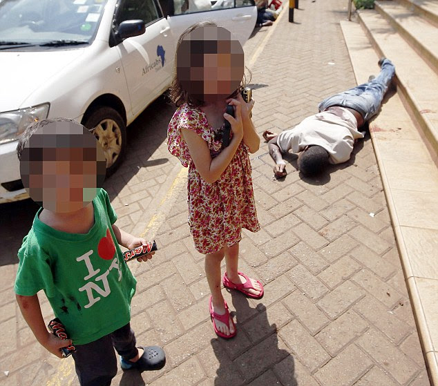 Amazing courage: The four-year-old boy with his sister, six, stands holding a Mars bar given to him by a terrorist outside the Westgate shopping centre in Nairobi