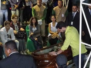 Roberto Rossi, filho do cantor, se apoia sobre o caixão antes do sepultamento (Foto: Katherine Coutinho / G1)