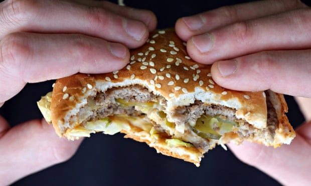 someone holding a hamburger