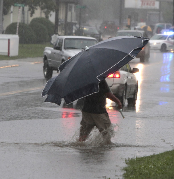 A pedestrian uses a beach umbrella to keep off the rain from tropical storm Irene on Sunday, Aug. 28, 2011 in Barre, Vt. Irene weakened to winds of 60 mph, well below the 74 mph dividing line between