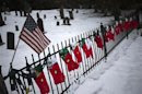 A U.S. flag hangs over stockings left as a memorial for victims of the Sandy Hook Elementary School shooting, along a fence surrounding the Sandy Hook Cemetery in Newtown