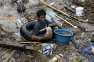 A resident rummages through debris following a flash flood that inundated Cagayan de Oro city, Philippines, Saturday, Dec. 17, 2011. A tropical storm triggered flash floods in the southern Philippines, killing scores of people and missing more. Mayor Lawrence Cruz of nearby Iligan said the coast guard and other rescuers were scouring the waters off his coastal city for survivors or bodies that may have been swept to the sea by a swollen river. (AP Photo/Froilan Gallardo)