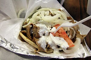 A gyro sandwich with meat, onions, tomato, and...