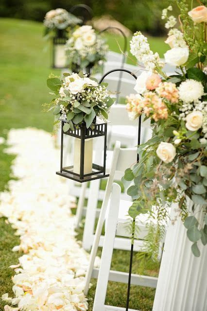 Lanterns with greenery and flowers along the aisle