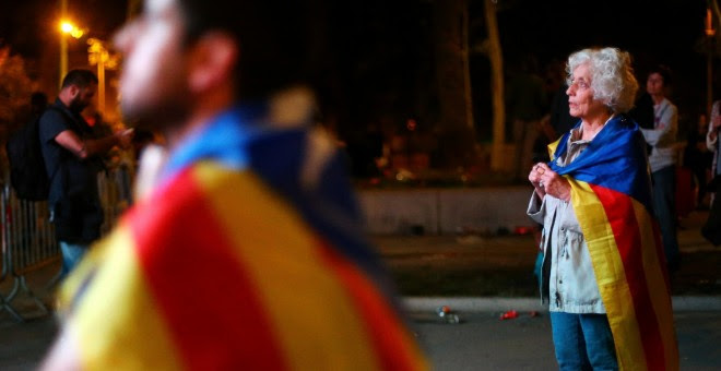 Varias de las personas que se concentraron en el Paseo Lluis Companys para seguir la intervención de Carles Puigdemont en el Parlament. REUTERS/Ivan Alvarado