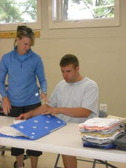 Vinnie Ireland and Supported Employment specialist Christine Denny fold EV Laundry customer's clothes.