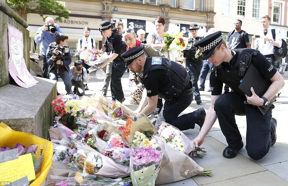 Oficiais de polícia deixam tributos na Praça St Ann, em Manchester.  A cidade ainda está tentando compreender o horror do ataque
