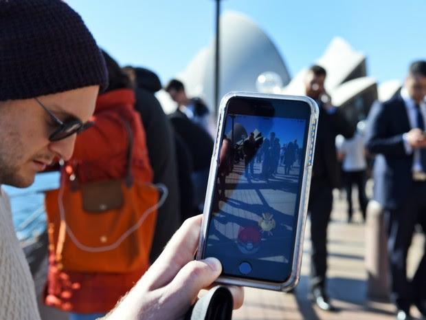 Dezenas de pessoas se reúnem para jogar Pokemon Go em frente à Ópera de Sydney, na Austrália. O aplicativo, baseado em um jogo da década de 1990, virou uma febre mundial onde os jogadores percorrem o o mundo real procurando monstros dos desenhos animados (Foto: William West/AFP)