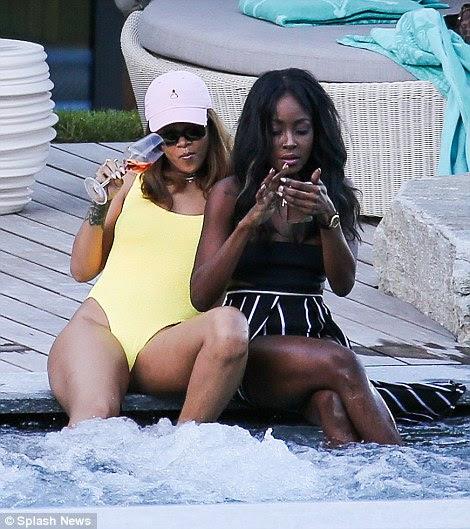 Não deixe cair o seguinte: O telefone parecia que poderia cair na piscina a qualquer momento como Rihanna se inclinou para trás e descontraído