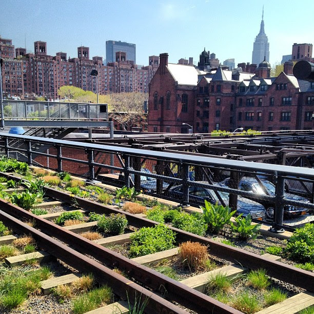 Old railroad tracks turned rooftop garden backed by car lift storage with an Empire State backdrop.