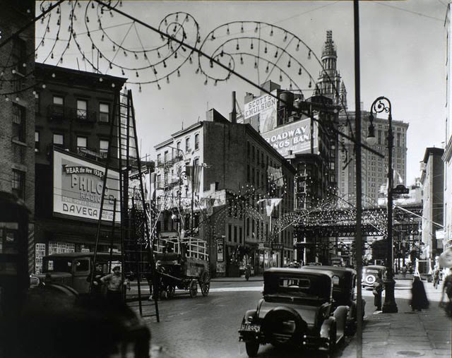 Oak and New Chambers Streets, Manhattan. Festive lights in curlicue designs arch over street, men with tall ladder, wagons, cars, billboards; 'el' and Municipal Bldg. just visible.