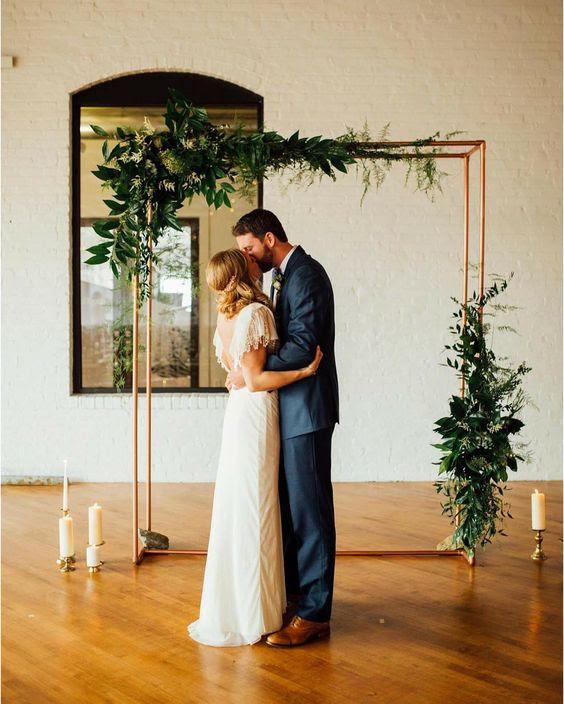 eine kupferne Hochzeit Bogen mit üppigem grün und Kerzen alles rund um