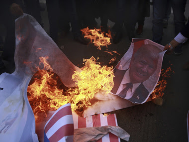 File image of Palestinians burn a poster of US president Donald Trump and a representation of an American flag, during a protest. AP
