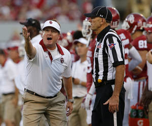 Photo - <p>OUcoach Bob Stoops pleads his case to an official during Saturday's 41-3 victory against Akron in Norman. [Photo by Bryan Terry, The Oklahoman]</p>