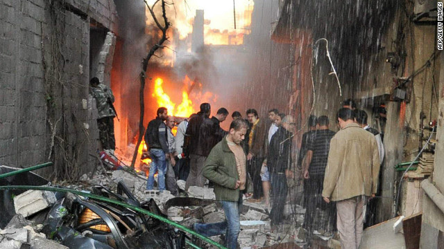 Syrian men inspect the scene of a car bomb explosion in Jaramana, a suburb of Damascus, on November 28, 2012.