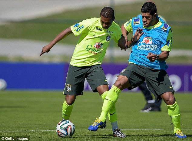 Solid: Fernandinho (left) holds off Hulk during Brazil training