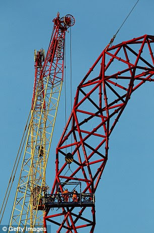Builders work on lowering the final piece to get the London 2012 ArcelorMittal Orbit sculpture completed