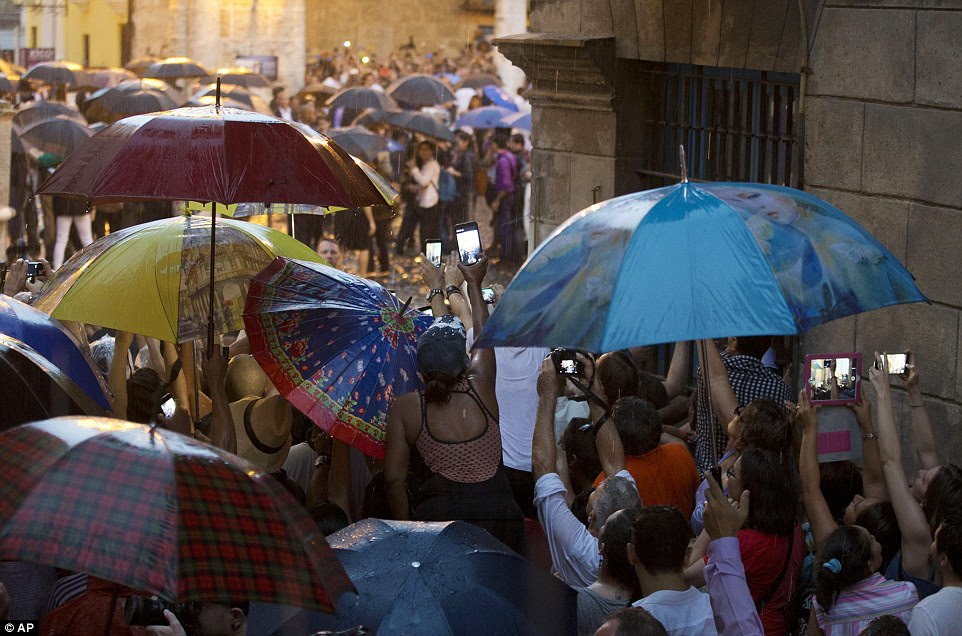 Historic: Cubans and tourists strain in the rain to get a glimpse of President Barack Obama as his delegation visits Cathedral Square in Old Havana