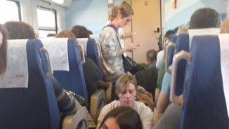 Passatgers a l'interior del vagó del tren de l'R15 a Sants (@TrensDignesEbre)