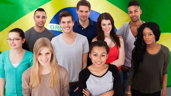 jovens diante da bandeira do Brasil
