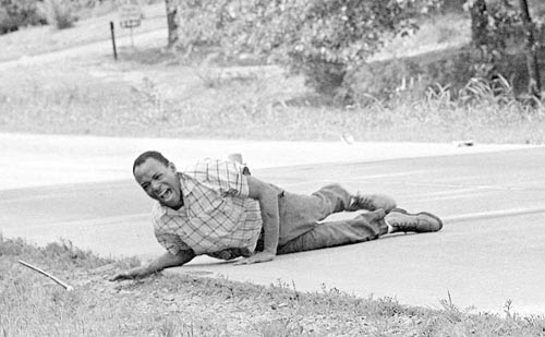 Civil rights activist James Meredith grimaces in pain as he pulls himself across Highway 51 in Hernando, Miss. after being shot during a voting rights march, June 6, 1966. by Pan-African News Wire File Photos