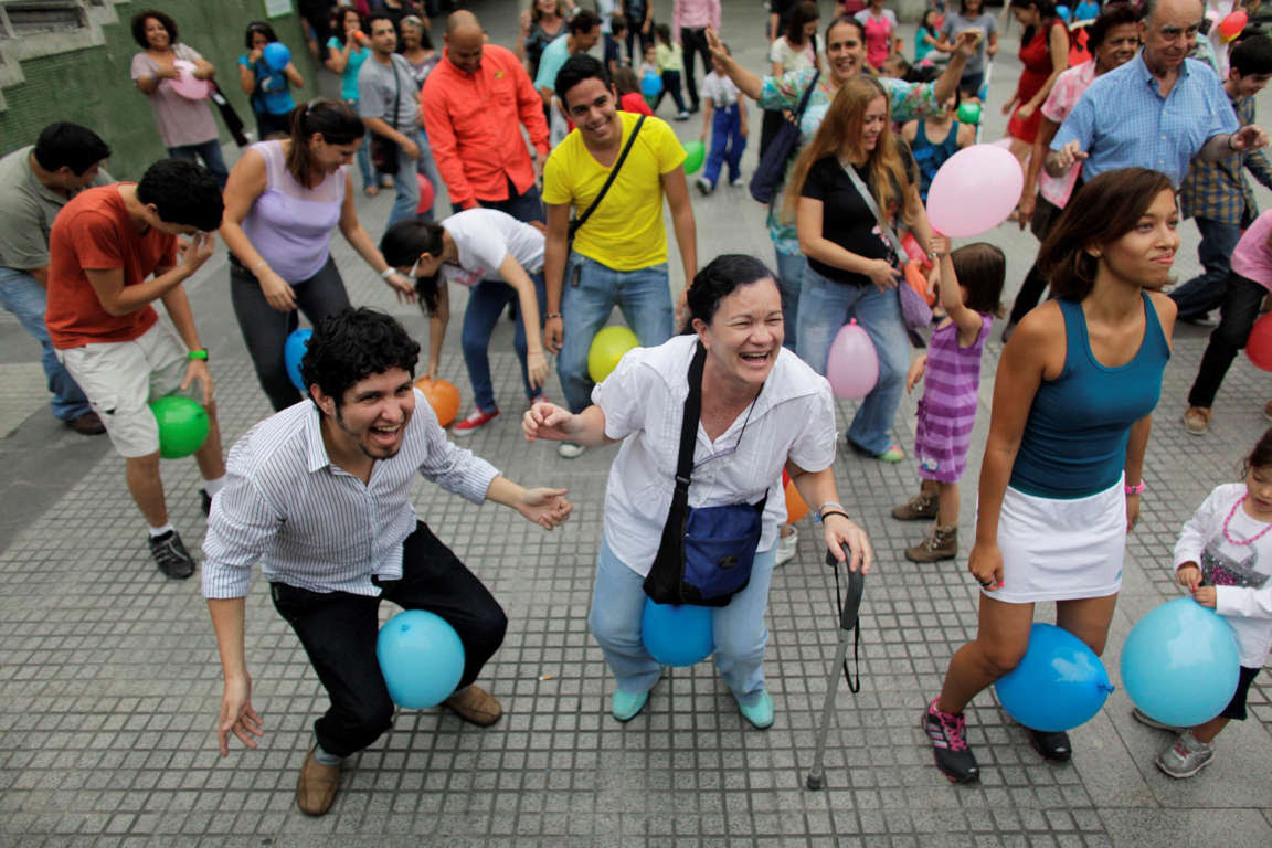 People laugh as they attend a session of laugh therapy in a plaza in Caracas, Venezuela, Tuesday, July 9, 2013. People attended the open session of laughter therapy with Venezuelan laughter therapist Menahem Belilty, who says that laughter has the healing powers to lift ones mood, enhance well-being and emotional balance, and in most cases helps people to overcome their problems. (AP Photo/Ariana Cubillos)