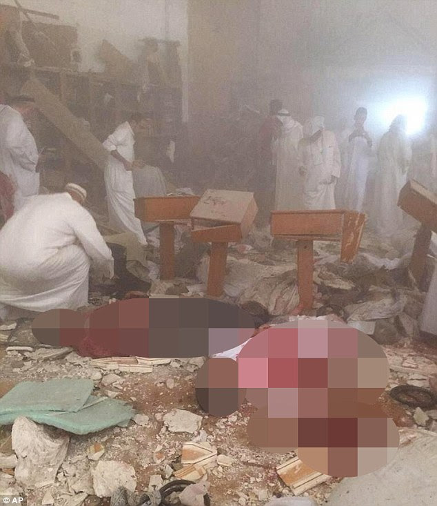 Aftermath: Mourners climb through the rubble and dust in the search for bodies after a suicide bomber killed 25 in Kuwait