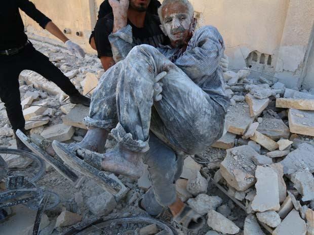Esquipes de resgate tiram homem síria de escombros nesta sexta-feira (25), depois que um helicóptero, supostamente do governo sírio, jogou um barril bomba no bairro Sakhour, na cidade de Aleppo (Foto: AFP PHOTO / AMC / ZEIN AL-RIFAI)