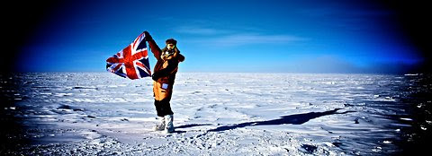 Alexander Kumar proudly displays his flag in the Antarctica wilderness.