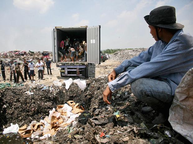 Funcionários do governo da Indonésia enterram cinco toneladas de carne de pangolim, encontradas com um contrabandista na região de Sumatra (Foto: Binsar Bakkara/AP)