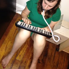 Playing the melodica on the kitchen floor