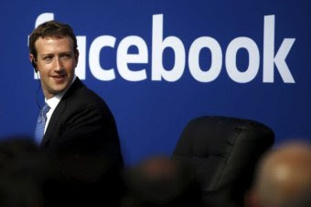 Mark Zuckerberg in front of a Facebook sign