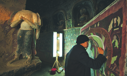 Painter Wu Shuangqin copies a wall painting in a cave of the Mogao Grottoes. Photo: CFP
