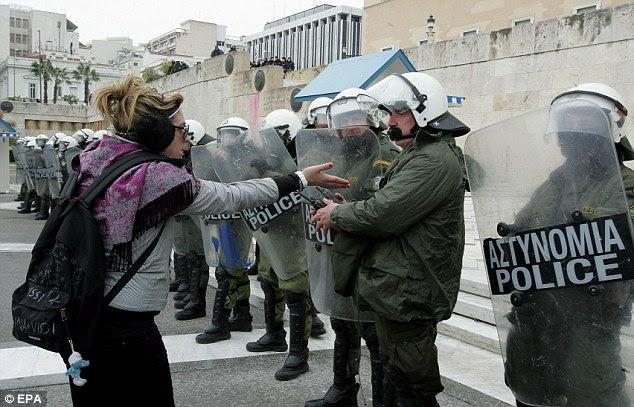 Επώδυνες περικοπές: Ένας διαδηλωτής remonstrates με την αστυνομία μπροστά από το Ελληνικό Κοινοβούλιο στην Αθήνα σήμερα κατά τη διάρκεια διαμαρτυρίας ενάντια στα νέα μέτρα λιτότητας