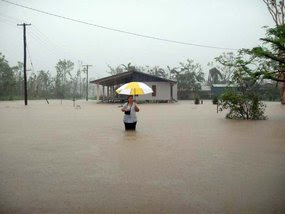A woman holding an umbrella stands in floodwaters as rain falls in Cardwell. March 8, 2011.