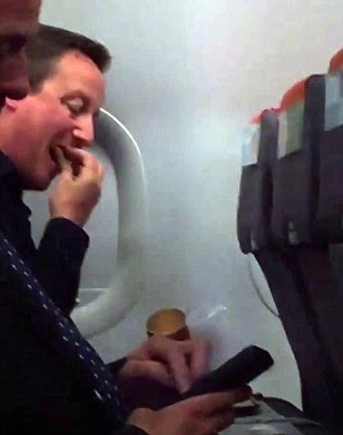 David Cameron is spotted scoffing Pringles while flying EasyJet