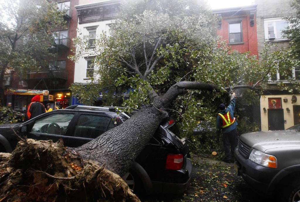 A workman cuts a tree in pieces after it fell on top of a car in Hoboken, New Jersey. Hurricane Sandy, one of the biggest storms ever to hit the United States, battered the densely populated East Coast, shutting down transportation, forcing evacuations in flood-prone areas and interrupting the presidential election campaign.