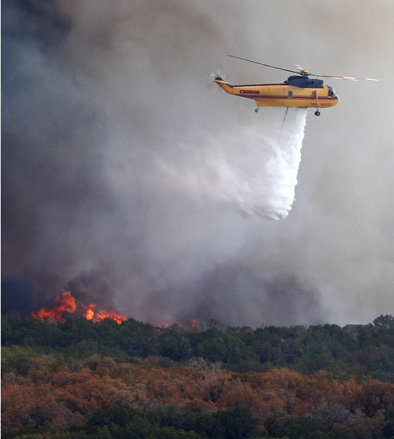A helicopter begins to drop water on a wildfire at Possum Kingdom Lake, Texas, Wednesday, Aug. 31, 2011.   Texas and Oklahoma are in the grips of a record-setting drought, and a summer of soaring temp