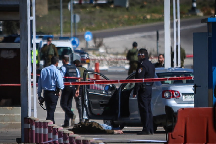 Israeli security forces standing by the body of a Palestinian attacker at the scene of shooting attack at a checkpoint near the Jewish settlement of Beit El in the West Bank before being shot dead, Jan. 31, 2016. (Flash 90)