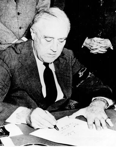 President Franklin D. Roosevelt signing the Declaration of War