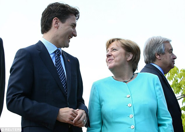 German Chancellor Angela Merkel and Canadian Prime Minister Justin Trudeau share a laugh during the G7 Summit in Italy on Saturday