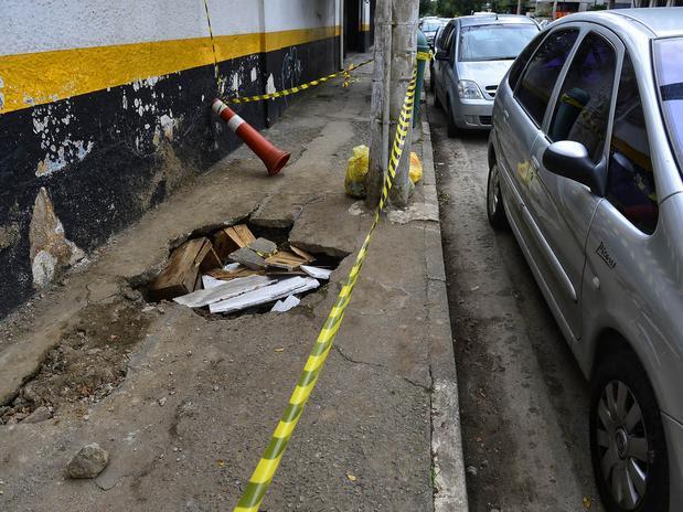 Na rua Cancioneiro Popular, um buraco provocou a interdição de parte de uma calçada. Foto: Fernando Borges / Terra