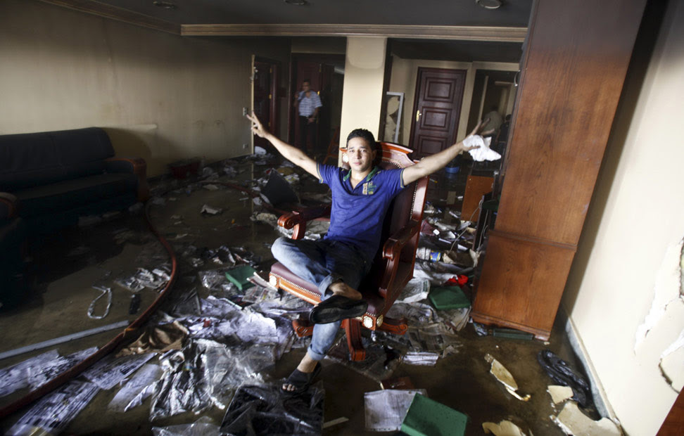 Un asaltante sentado en una de las sillas de la sede de los Hermanos Musulmanes después de haber sido incendiada por los protestantes opositores del presidente Mursi. Cientos de personas lanzaron cócteles molotov y piedras contra el edificio e intercambiaron disparos con los miembros de los Hermanos Musulmanes en el interior. REUTERS/Amr Abdallah