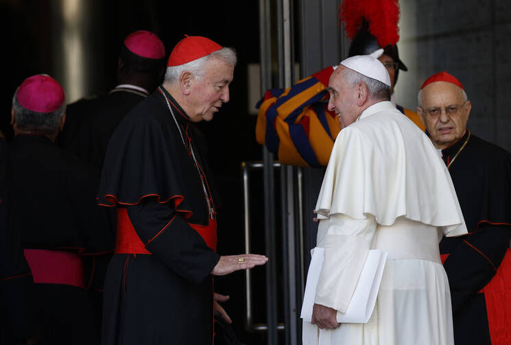 Cardinal Vincent Nichols of Westminster, England, talks with Pope Francis as the arrive for the concluding session of the extraordinary Synod of Bishops on the family at the Vatican Oct. 18. At right is Cardinal Lorenzo Baldisseri, general secretary of the Synod of Bishops. (CNS photo/Paul Haring)