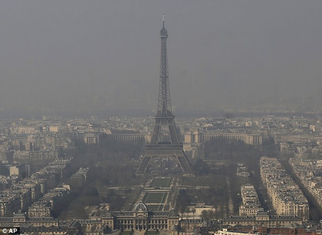 The Eiffel Tower, is barely seen through the smog from Paris. Drivers in Paris will only be allowed to use their cars every other day from tomorrow because of dangerous pollution levels