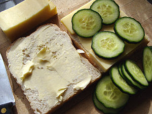 Making cheese and cucumber sandwiches
