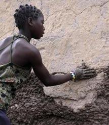 Una mujer repara sus casa, destruida por las inundaciones. / Intermon Oxfam